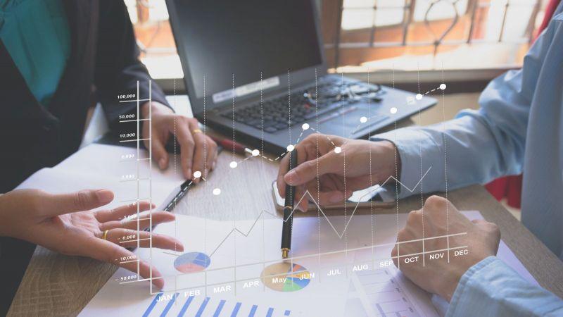 Arbeistsituation mit zwei Paar Händen einem Laptop und einem Papier mit Grafiken und Diagrammen