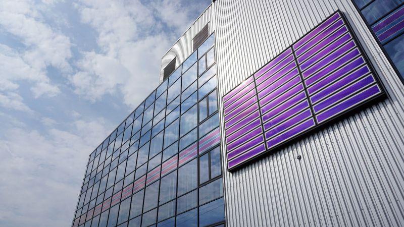 In die Fassade eines großen Gebäudes sind großflächige, blau scheinende Photovoltaik-Module integriert.