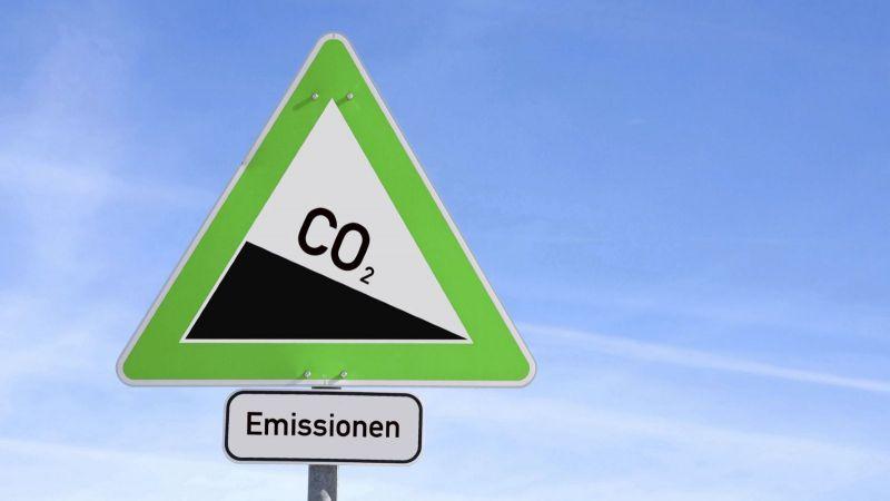 Ein Verkehrsschild, auf dem CO2 bergab dargestellt wird.