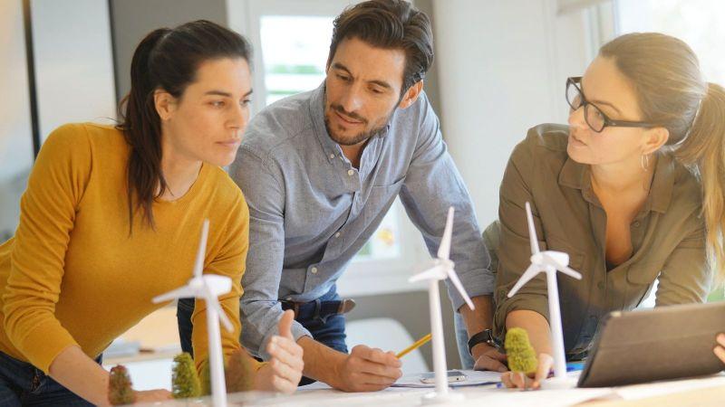 Drei Kolleg*innen planen anhand von Modellen von Windenergieanlagen.