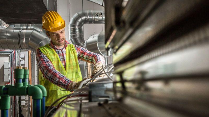 Ein Handwerker arbeitet an einer Klimaanlage