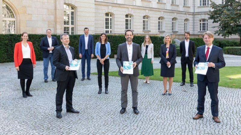 Gruppenfoto im Rahmen der Übergabe der Forschungsagenda, Personen halten Broschüre in der Hand