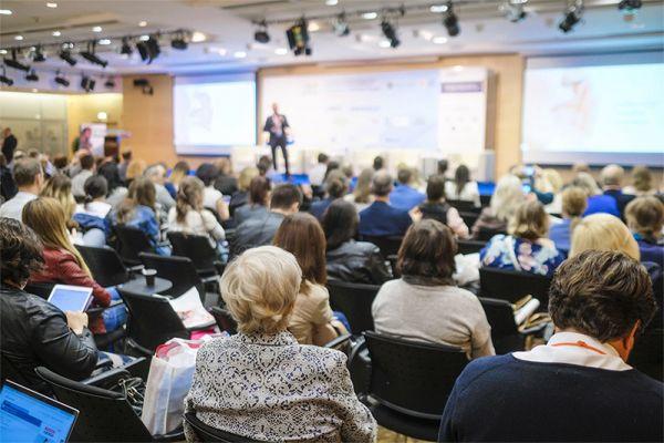 Symbolbild: Teilnehmer einer Veranstaltung blicken auf ein Podium, wo eine Person einen Vortrag hält.