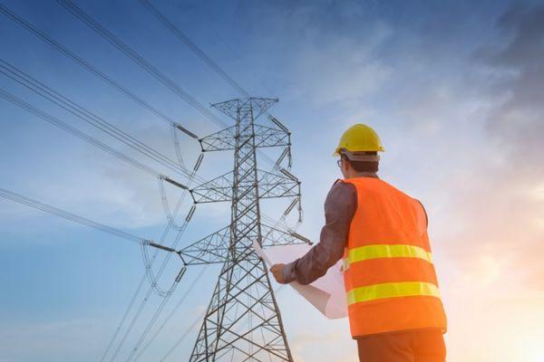 Bauarbeiter steht vor Strommast
