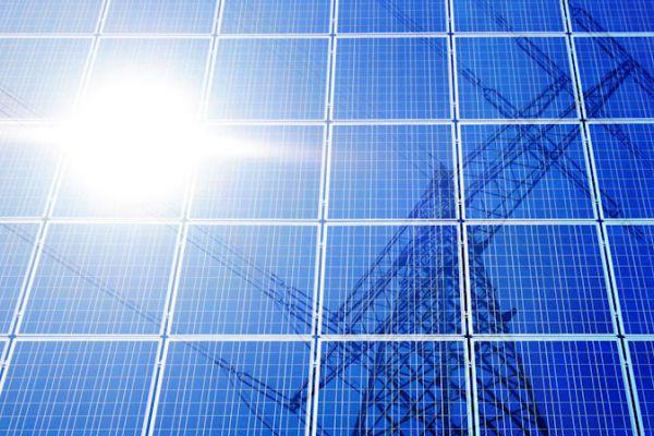 Zu sehen ist, wie sich die Sonne und ein Strommast auf einem Photovoltaik-Modul spiegeln.