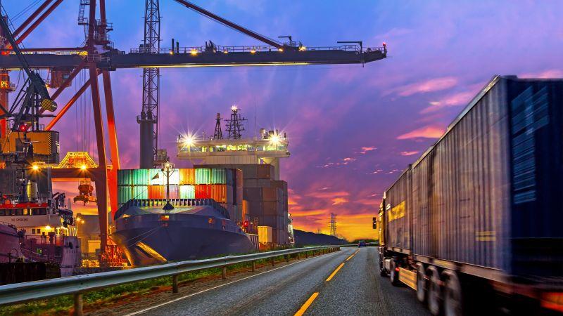 Symbolbild Energiewende in der Industrie: LKW fährt in Abenddämmerung an Bausstelle mit Kran vorbei.