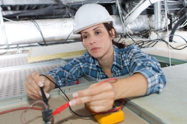Bauarbeiterin mit Helm repariert Stromleitung