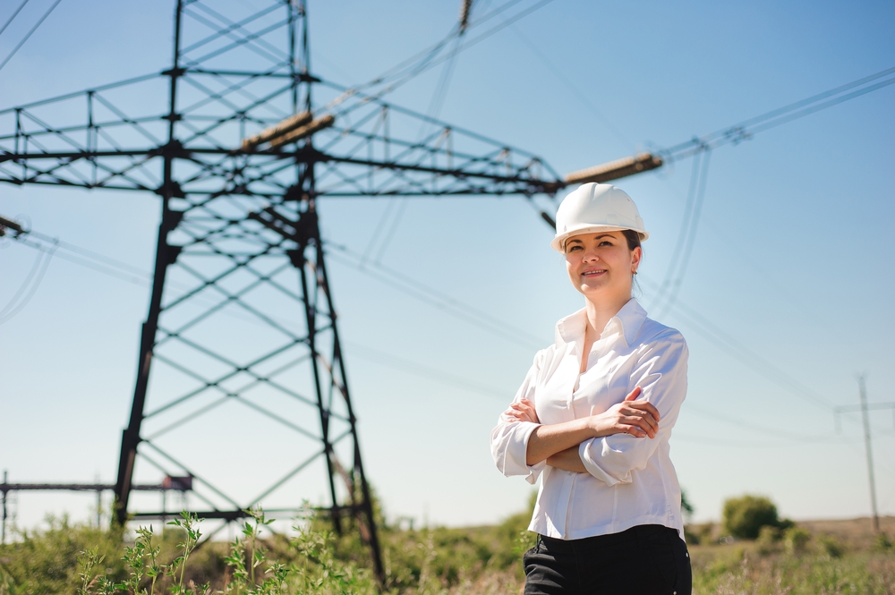 Ingenieurin vor einer Stromleitung auf einem Feld