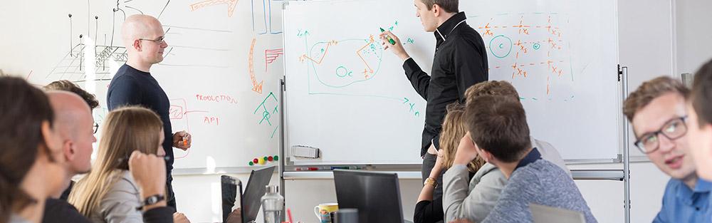 Personen mit PC und Notizblöcken am Tisch blicken auf beschriftetes Board, an dem einer der Gruppe etwas erklärt