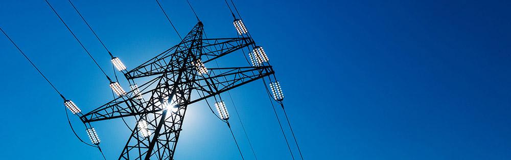 Strommast vor blauem Himmel